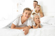 Happy family lying in bed at home