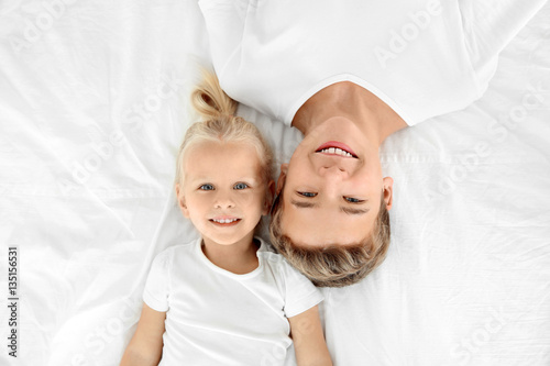 Cute little girl with elder brother lying on bed