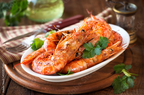 Valokuvatapetti Grilled King prawns or shrimps with parsley on white plate on dark rustic wooden