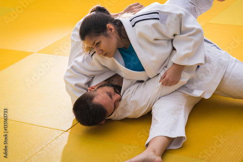 Foto op Plexiglas Vechtsport Woman and man judo fighters in sport hall