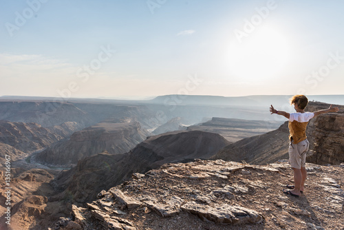 Obraz na plátně  Rear view of tourist looking at expansive view over the Fish River Canyon, scenic travel destination in Southern Namibia