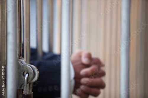 Fotografie, Tablou  hand of businessman in jail as background with blur copyspace.
