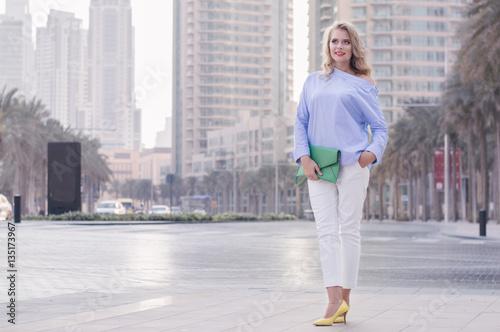 Photo  Smiling european female with blond hair standing near empty road in Dubai, UAE