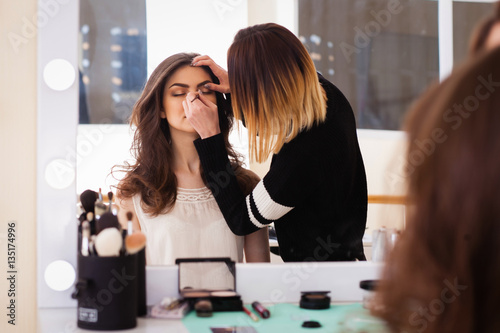 Fotografía  make-up artist doing make-up girl in the salon, beauty concept