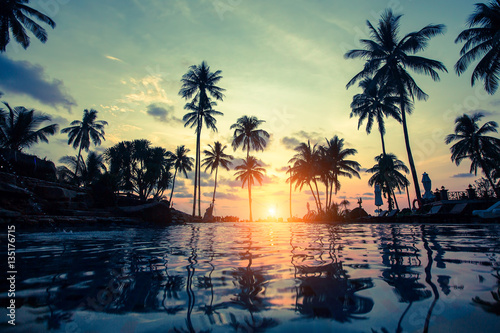 Wall Murals Bali Tropical beach with pool and silhouetted palm trees during sunset.