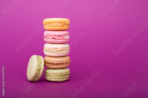 Papiers peints Dessert Sweet and colorful French macaroons or macarons biscuits on purple background