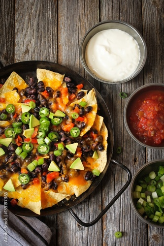 Fotografía  Classic Nachos with Tortilla chips melted cheese sauce jalapeno peppers avocado