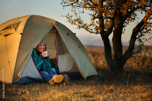Young woman in sports wear and trekking shoes sitting in bivouac Canvas Print