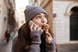 Woman with ice cream talking on cell phone in city