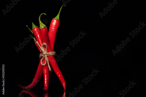 Red hot chilly peppers tied on a black background
