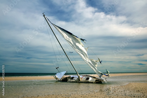 Foto op Canvas Schipbreuk The yacht is shipwrecked and thrown ashore, torn sail. Gulf Coas