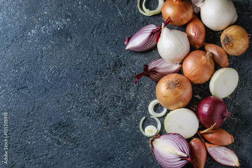 Fotografia Variety of whole and sliced red, white, yellow and shallot onions over dark stone texture background
