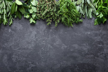 Fototapetafresh herbs on dark stone background with space for text