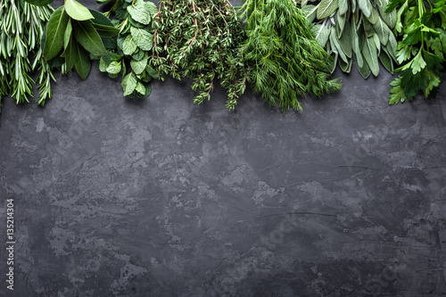 fresh herbs on dark stone background with space for text
