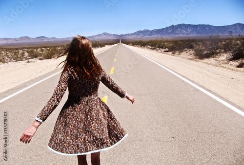 Woman walking along road, rear view, California, USA