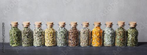 Fototapeta Different kinds of herbs for tea inside glass bottles. obraz