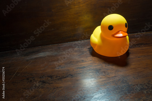 Yellow rubber duck on the table wood dark tone - Buy this stock ...