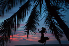 Woman Silhouette Dancing On Beach At Sunset