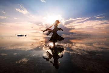 Elegantna žena koja pleše na vodi. Zalazak sunca i silueta.