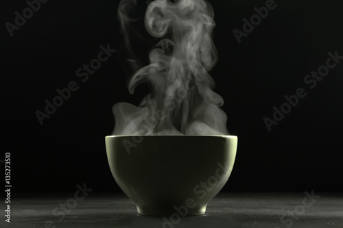 Cuadros en Lienzo A bowl of hot food and steam on dark background.
