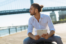 Young Businessman In NYC Holding A Digital Device