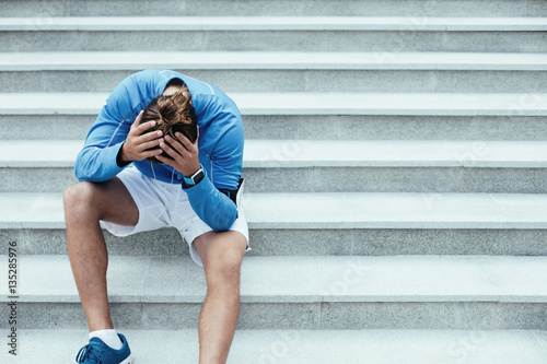 Fototapeta  Upset athlete after failure sitting on the stairs on the street and holding his