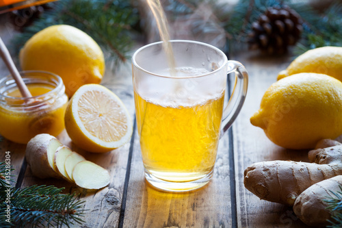 Photo sur Toile The Vitamin black tea with ginger, lemon and honey poured in a cup with steam on a wooden table vintage. Healthy drink. Hot winter beverage concept. Antiviral useful drink.