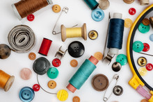 Threads, Needles, Buttons And Other Sewing Stuff On A White Background, Flat Lay Composition, Top View.