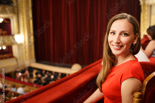 Young smiling woman in red dress sitting on balcony in the theatre