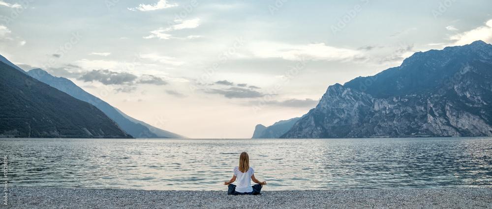 Fotografia Woman meditating at the lake