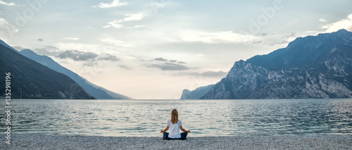 Staande foto School de yoga Woman meditating at the lake