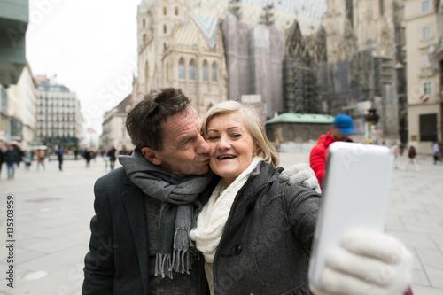 Beautiful senior couple on a walk in city centre taking selfie. Wallpaper Mural