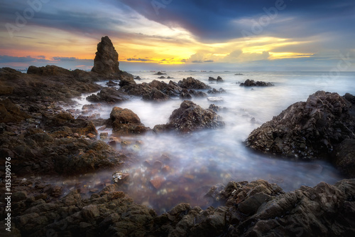 Keuken foto achterwand Crimson Seascape of sea with dramatic wave and rock in sunset.