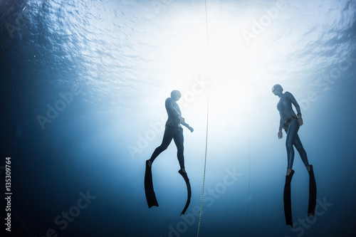 Two free divers, man and woman, ascending from the depth Canvas Print