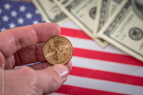 Photo  one dollar coin in hand against usa flag
