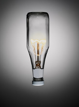 Ketchup Bottle With Light Bulb In It Against Graduated Grey Background