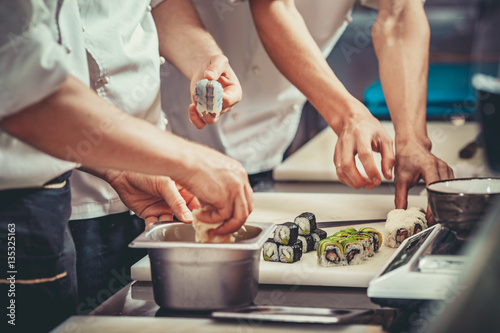 Poster Sushi bar Three cooks in hotel or restaurant kitchen decorating dish. They are working on maki rolls. Preparing sushi set. Only hands