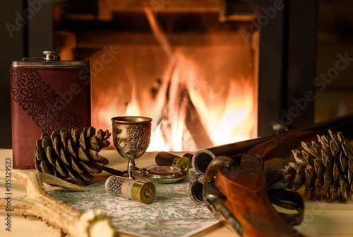 Foto op Canvas Jacht Knife Compass and map lie by the fire. In a fireplace fire burns.