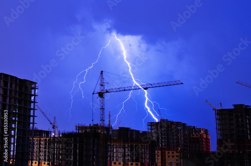 Foto op Plexiglas Onweer Lightning storm crane weather industrial city building construction night flash