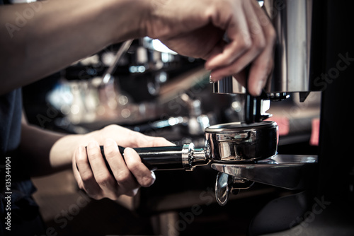 Fotografie, Obraz  Barista making coffee with machine,stamp tool in cafe in vintage