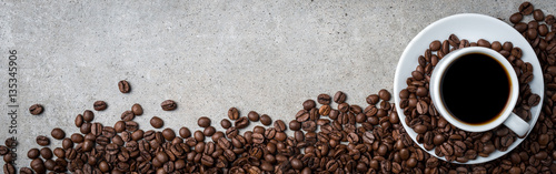 Photo sur Toile Salle de cafe Cup of coffee with coffee beans on gray stone background. Top view