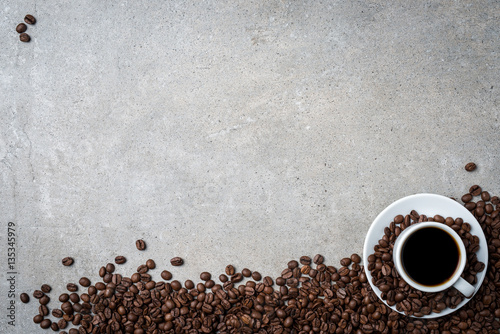 Poster Café en grains Cup of coffee with coffee beans on gray stone background. Top view