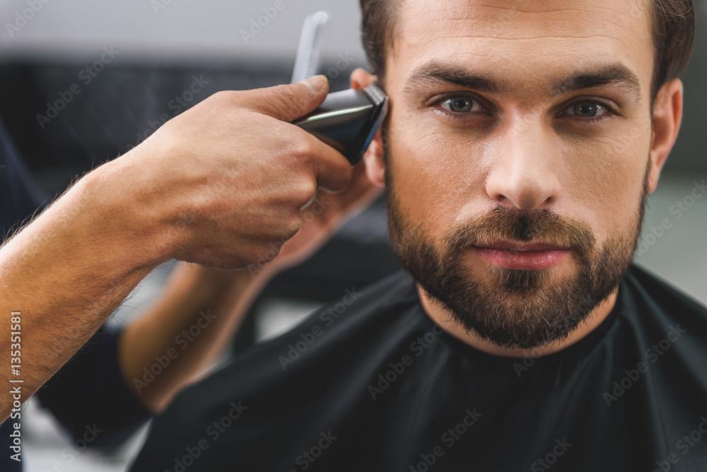 Fototapeta Confident guy sitting at beauty salon