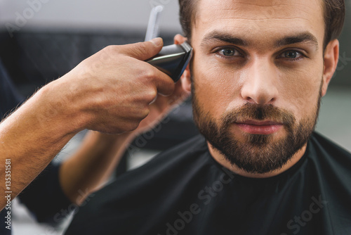 Confident guy sitting at beauty salon