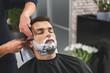 Professional hairdresser shaving beard of customer