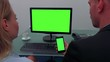 A man and a woman sit at a desk in an office and look in turns at a computer screen and a smartphone (both green screen)