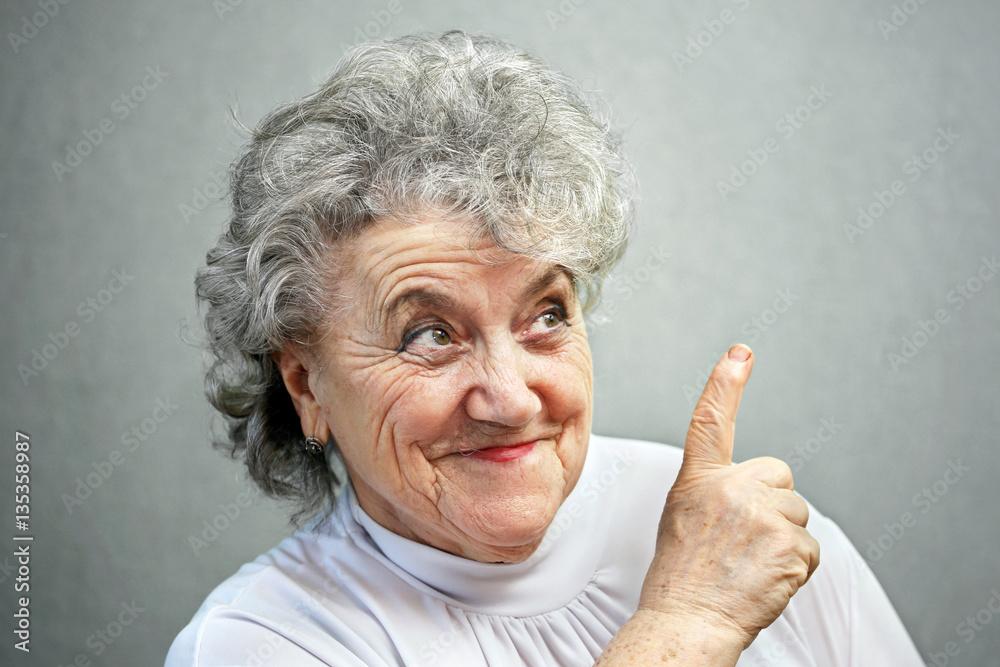 Fototapety, obrazy: Thoughtful grandmother points a finger up