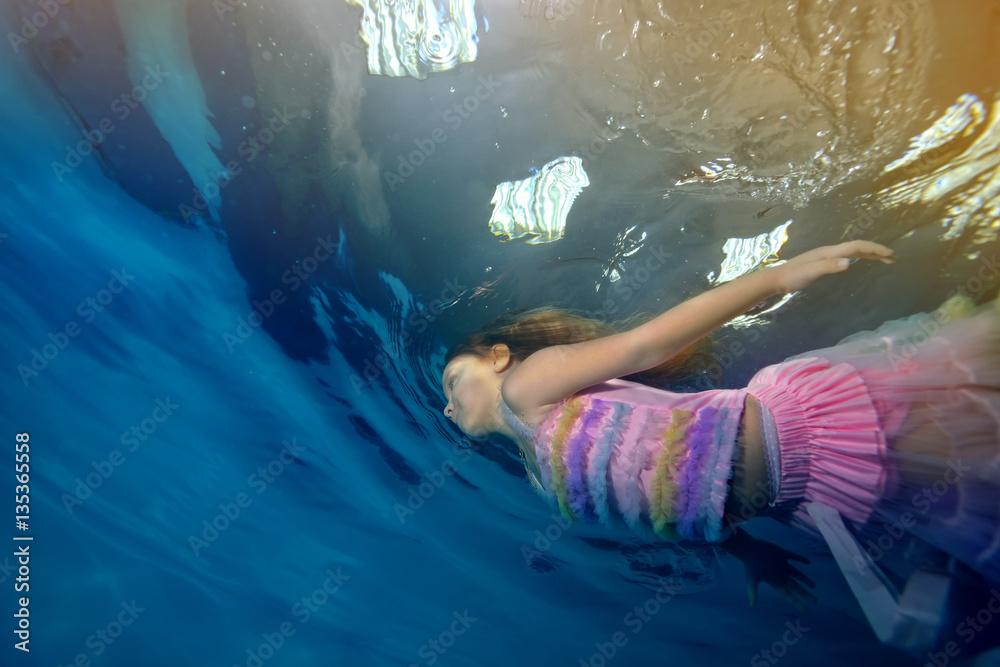 Little girl swimming underwater in a beautiful dress on a background of lights and light. Portrait. Shooting under the water surface. Landscape orientation