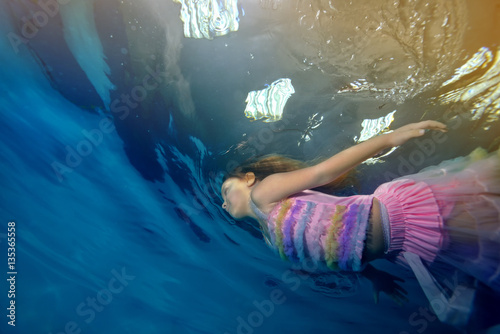 Fototapety, obrazy: Little girl swimming underwater in a beautiful dress on a background of lights and light. Portrait. Shooting under the water surface. Landscape orientation