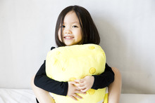 Asian Girl Holding Yellow Plush Toy